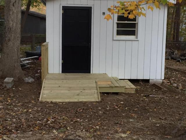 Steps and ramp constructed out of wood to for easier access to the shed it is attached to.