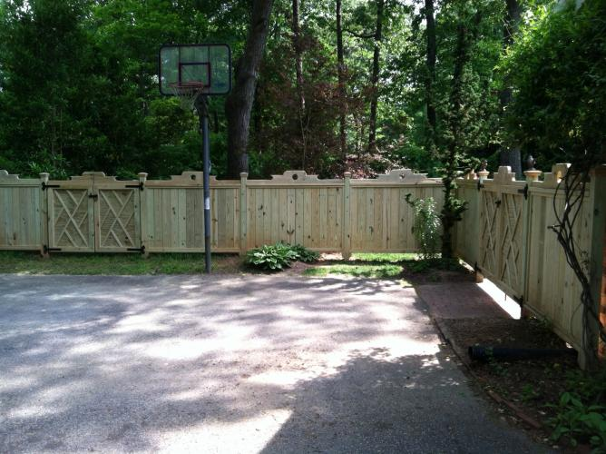 Fence surrounding a basketball court in a client's backyard.