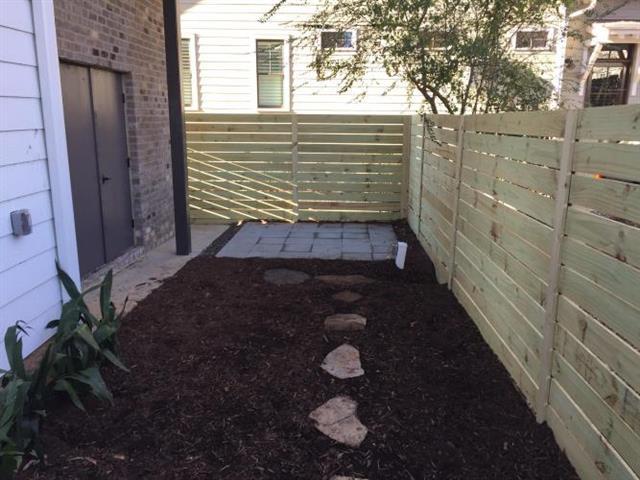 Fence, patio, and fresh mulch in a backyard.