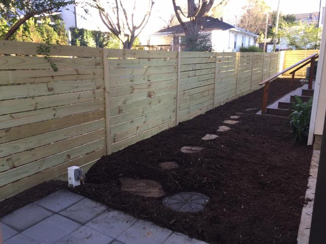 Fence with landscaping installed in a backyard.