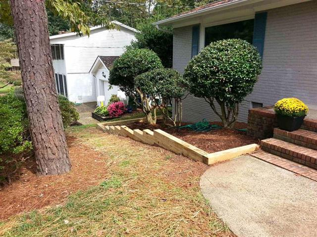 Recently pruned shrubs in a home's front landscape bed with a new wood border.