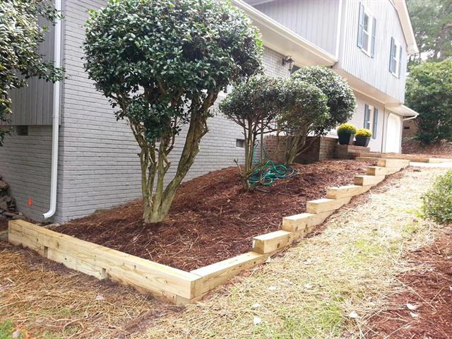 Stair step wood border around a home's front landscaping bed.