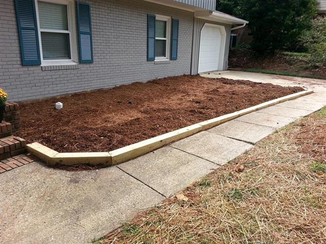 Brand new landscaping bed with a wood border between the home and walk to front door.