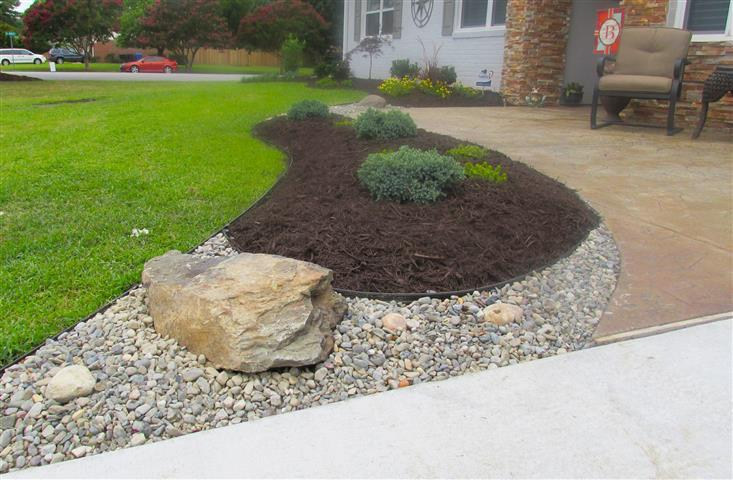 Landscape bed with rocks, mulch, and plants installed by FortSmith Landscaping.