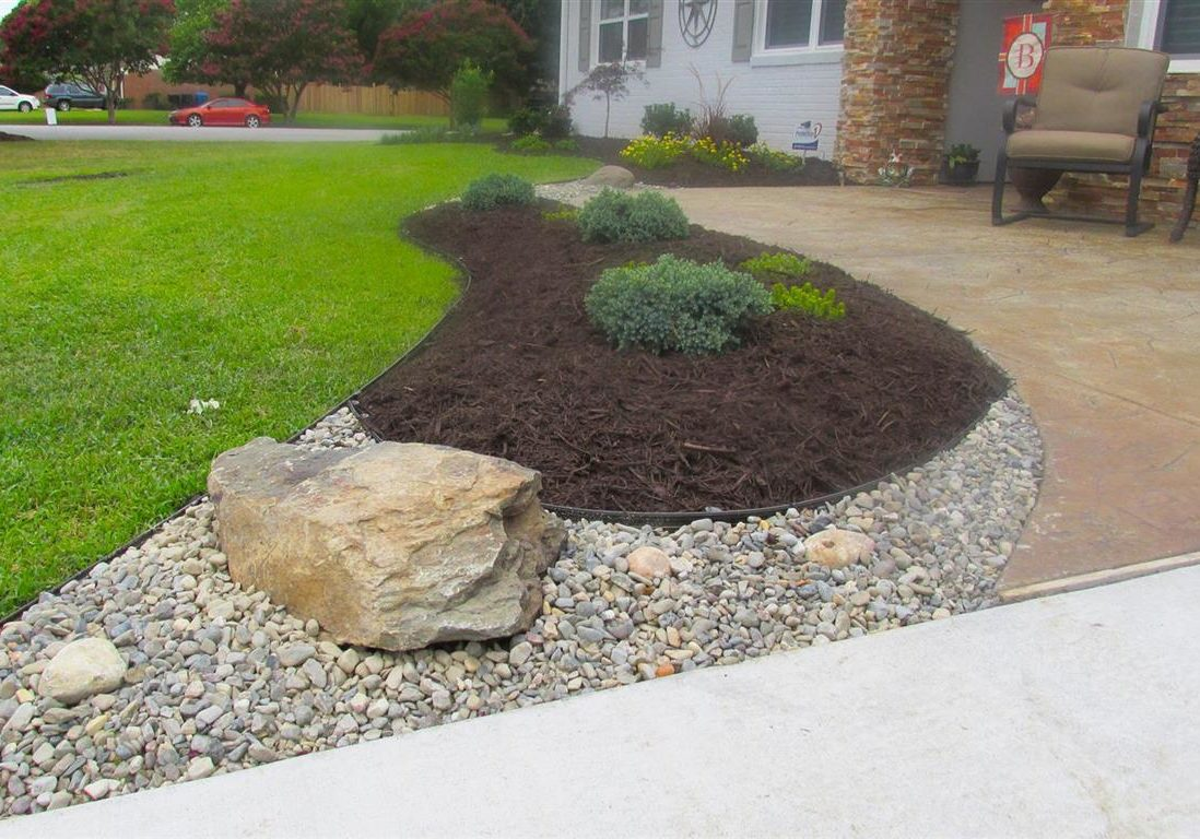 Landscaping installed in front of a home with river rock, mulch, and plants.